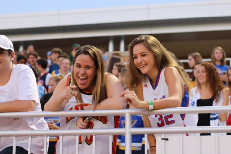 Sophmores Katherine Lucier and Lizzy Feinberg cheer on the football team from the stands.