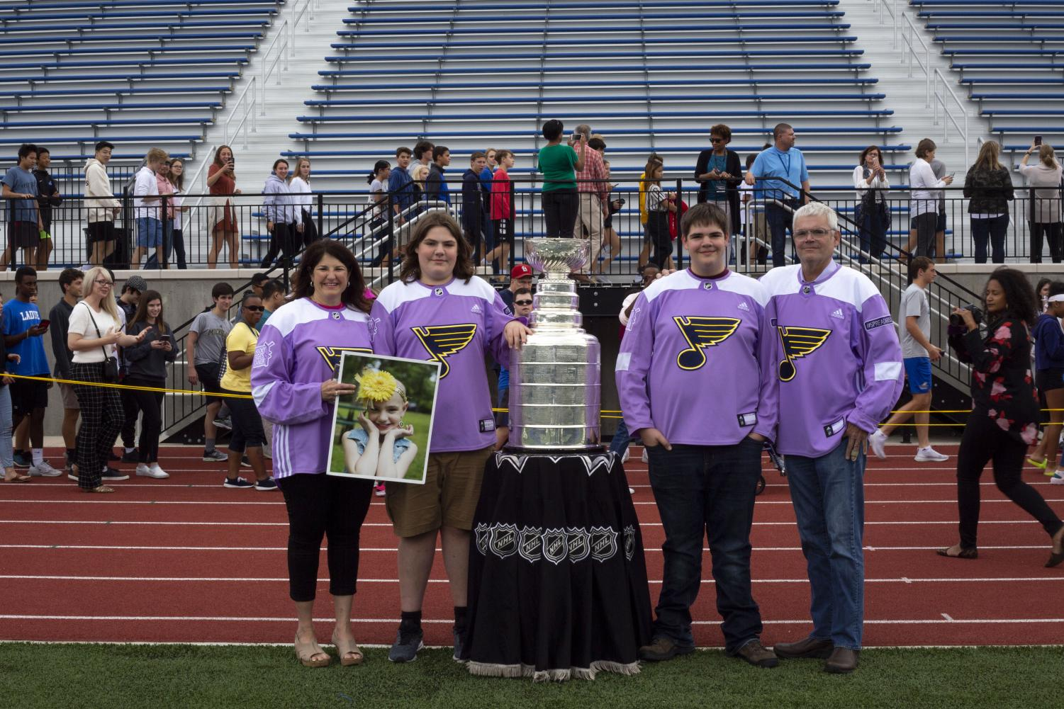 The Dougan family poses with the Stanley Cup on Ladue High School's football field Oct. 3. The Stanley Cup was brought to Ladue as a surprise for the Dougans to honor their sister, Ari Dougan, who passed away nearly two years ago.