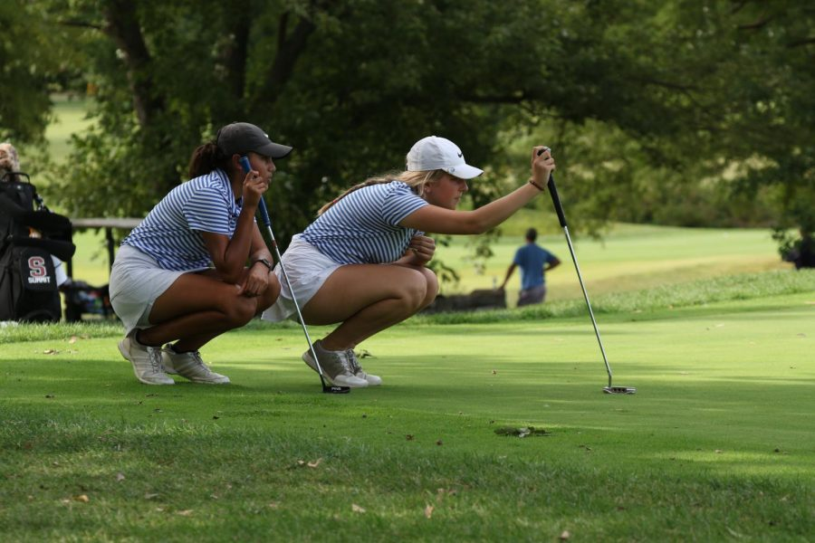 Senior Kacy Spratt and junior Meera Upadhyay look closely after a putt shot Sept. 24th 2021. Both Spratt and Upadhyay have been on varsity since freshman year. They played the match against Rockwood Summit.