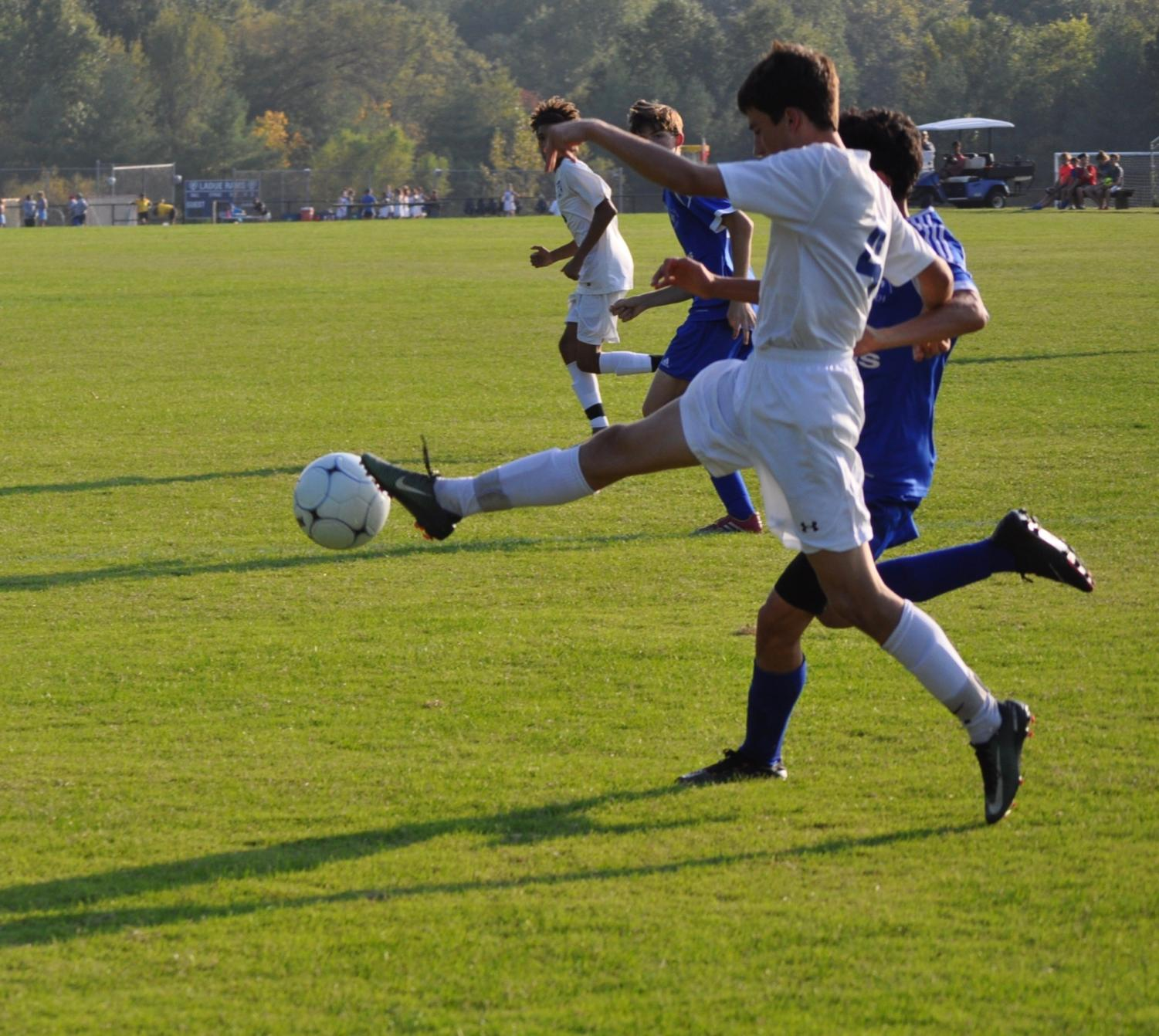 Freshman Grant Garland challenges the SLUH player for the ball.