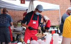 Max Yang helps cooks at the Seinen Kai booth put toppings on Okonomiyaki for the customers.